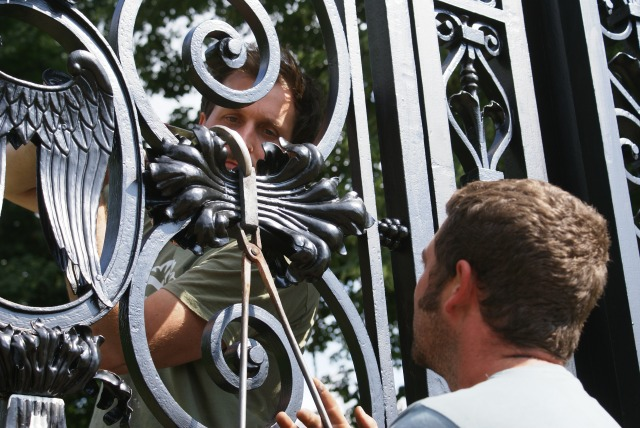 'Tijou' gates, Andy and Ben fitting one of the last forged collars to a pre-painted reproduction acanthus decoration on the gate frame.